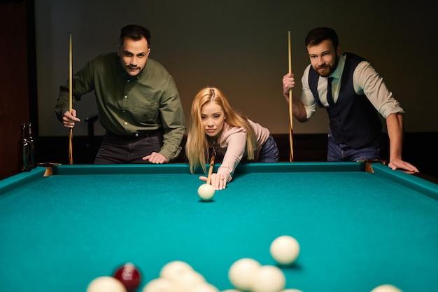Frau, die ratschläge zum schießen des poolballs beim billardspielen mit freunden erhält, konzentriert auf sportspiel