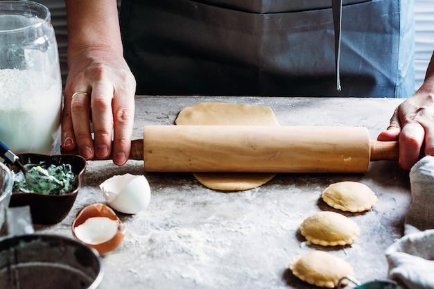 Frau, die ravioli auf tabelle macht. italienische küche und glutenfrei