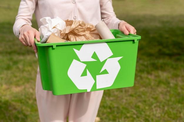 Frau, die recylcing korb hält