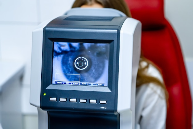 Frau, die refraktometer-sehtestmaschine in der augenheilkunde betrachtet