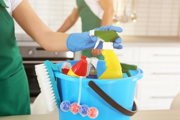 Frau, die reiniger vom eimer mit waschmitteln, nahaufnahme nimmt
