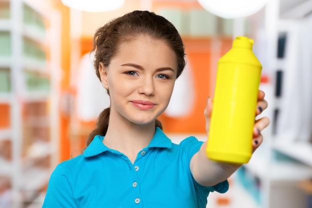Frau, die reinigungsmittel im gebäude hält
