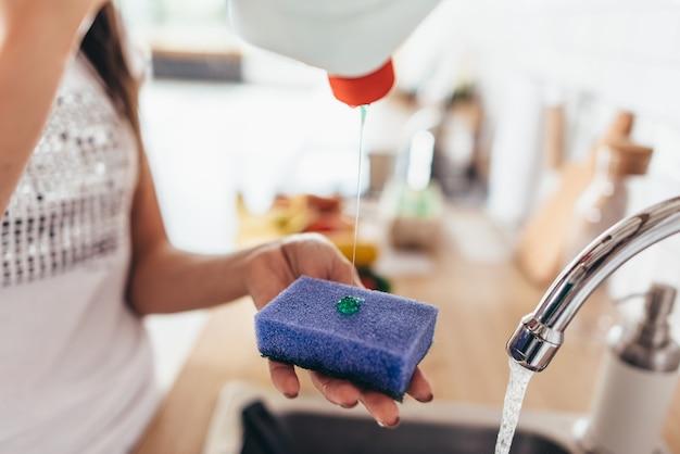 Frau, die reinigungsmittel zu einem schwamm setzt, um pfanne in der küchenspüle zu waschen. handgeschirr spülen. nahansicht.