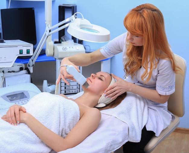 Frau, die reinigungstherapie mit einem professionellen ultraschallgerät im kosmetikbüro erhält