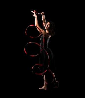 Frau, die rhythmische gymnastik mit band auf schwarzem hintergrund tut