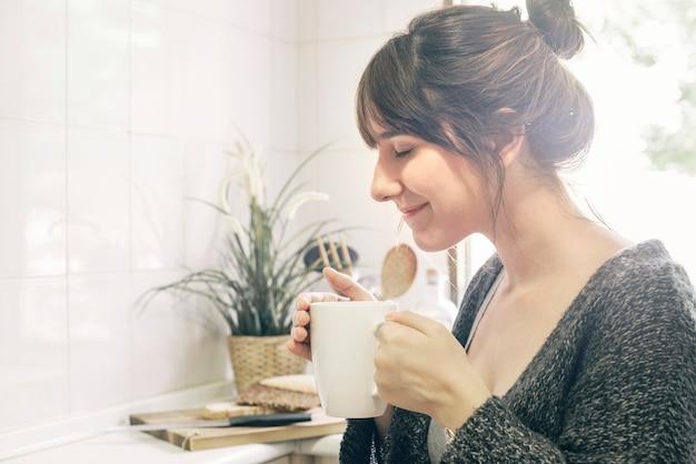 Frau, die riechenden kaffee der schale hält