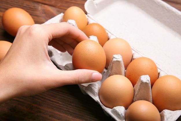 Frau, die rohes ei aus der verpackung auf holzuntergrund nimmt