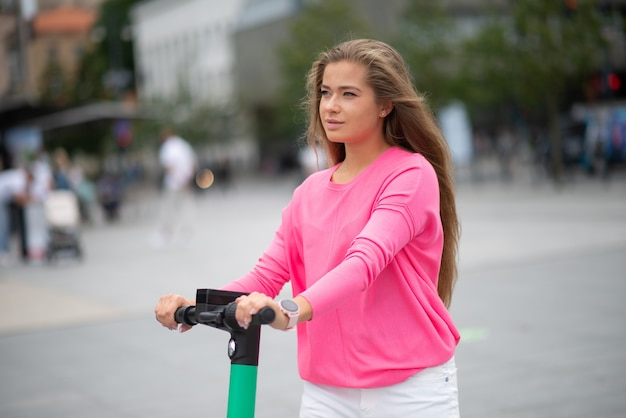 Frau, die roller in einer stadt, städtischer mobilität und nachhaltigem ökologischem transportkonzept fährt