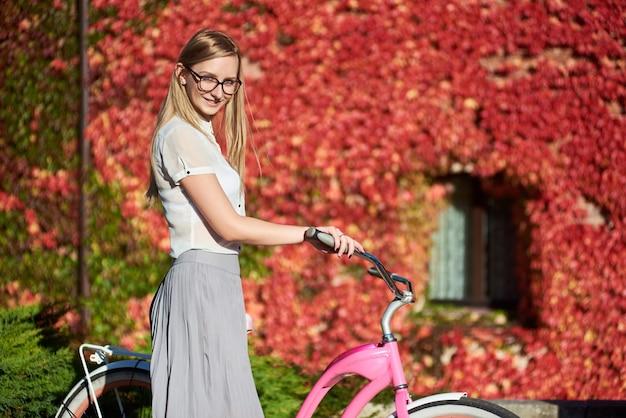 Frau, die rosa dame fahrrad fährt