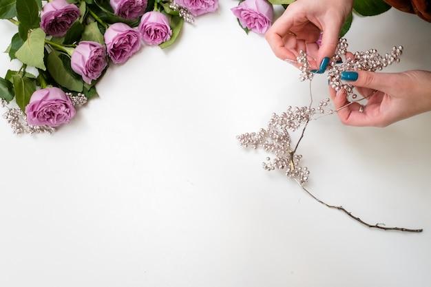 Frau, die rosa rosen mit silbernen perlen auf weißem hintergrund verziert. hochzeits- oder partyflorist bei der arbeit. kreativer lebensstil