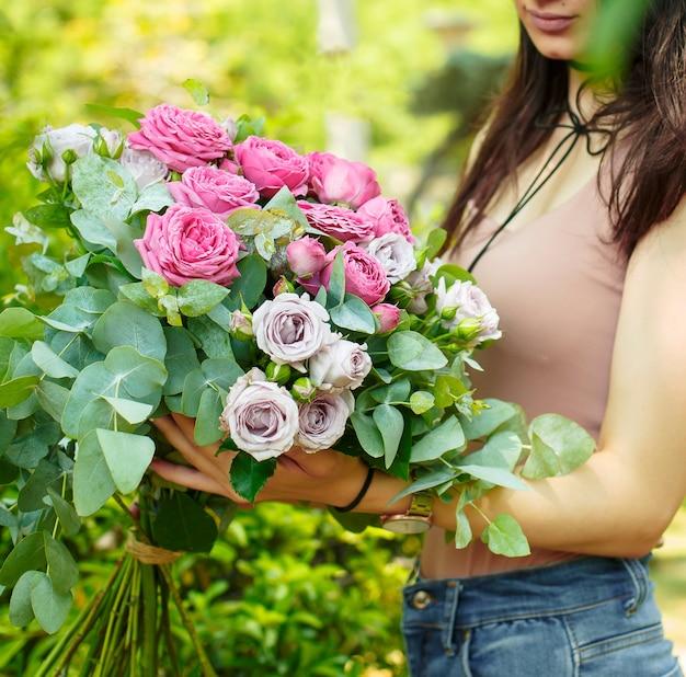 Frau, die rosa rosenstrauß mit eukalyptusblättern im garten hält