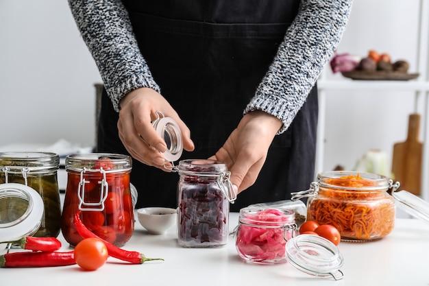 Frau, die rote beete für die gärung am tisch in der küche vorbereitet