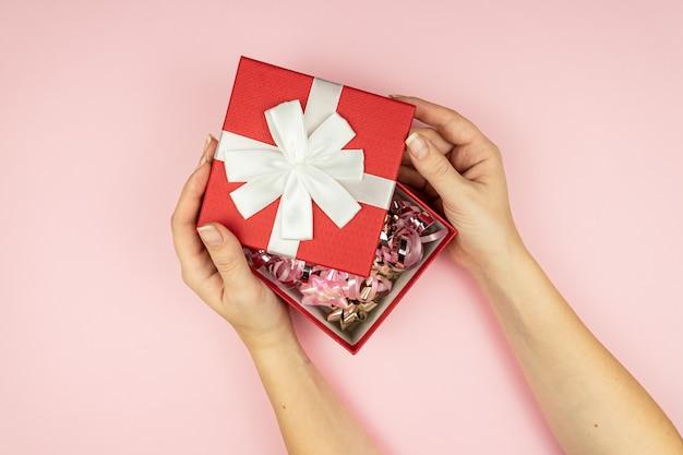 Frau, die rote geschenkbox auf rosa oberfläche hält