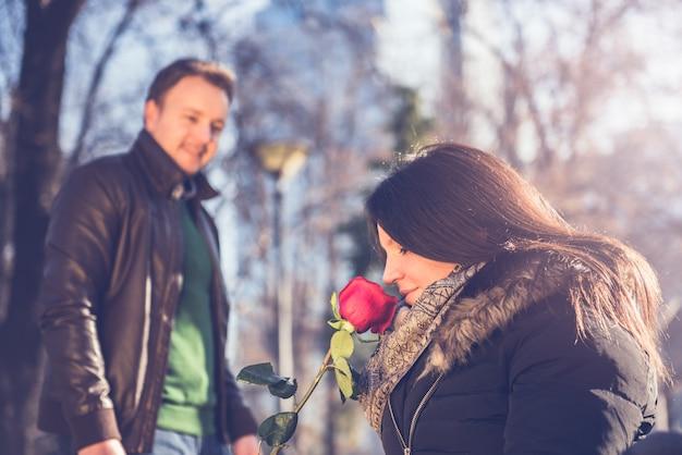 Frau, die rote rose riecht