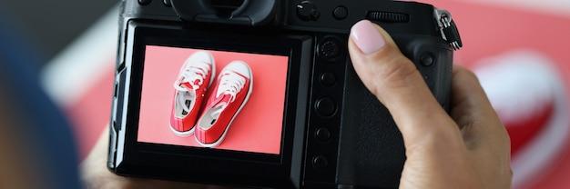 Frau, die rote sportschuhe auf professioneller kameranahaufnahme fotografiert