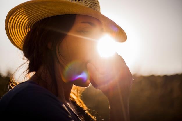 Frau, die roten apfel im sonnenlicht isst
