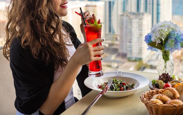 Frau, die roten cocktail am restaurant mit stadtansicht trinkt