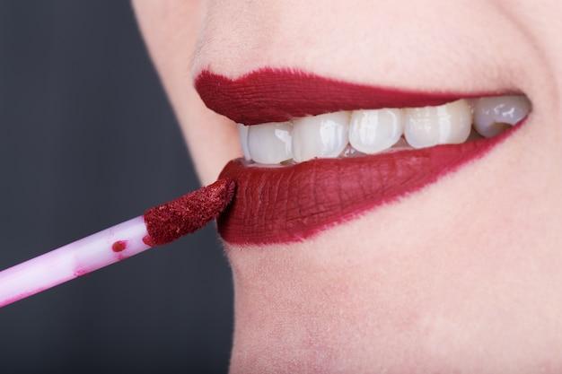 Frau, die roten lippenstift auf ihren lippen anwendet