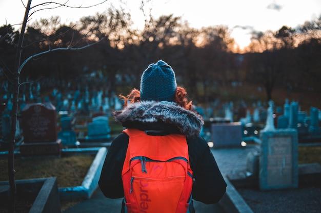 Frau, die roten rucksack in einem friedhof trägt