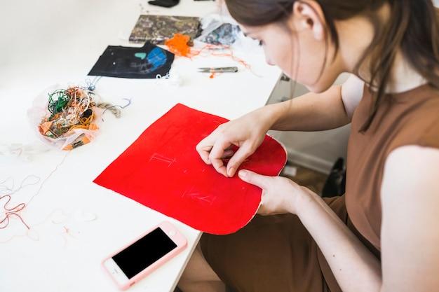 Frau, die roten stoff mit nadel näht