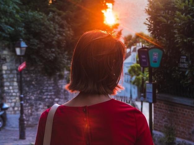 Frau, die rotes betrachten des sonnenuntergangs trägt