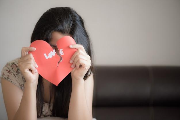 Frau, die rotes defektes herz mit liebestext hält. valentinstag-konzept.