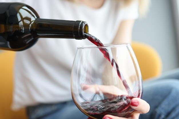 Frau, die rotwein in glasnahaufnahme gießt