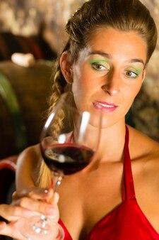 Frau, die rotweinglas im keller betrachtet