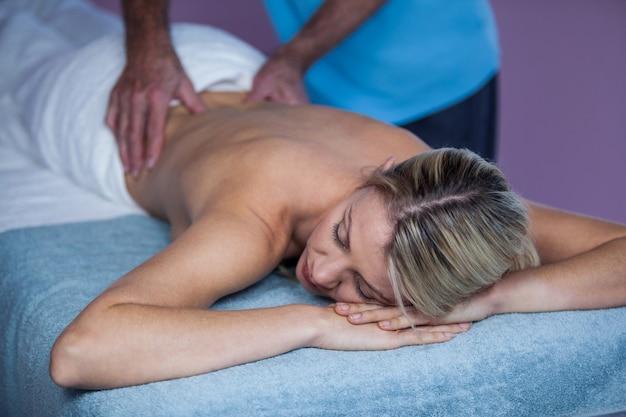 Frau, die rückenmassage vom physiotherapeuten erhält