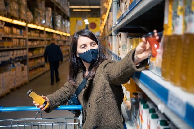 Frau, die saft im lebensmittelgeschäft in medizinischer maske wählt