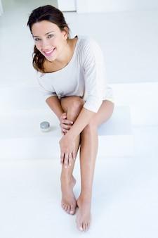 Frau, die sahne auf beinen anwendet
