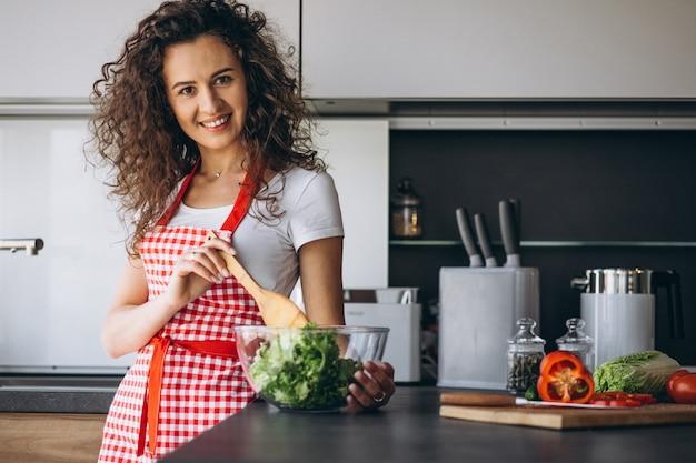 Frau, die salat an der küche macht
