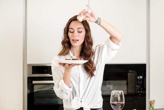 Frau, die salz auf dem fleischteller an der küche verwendet