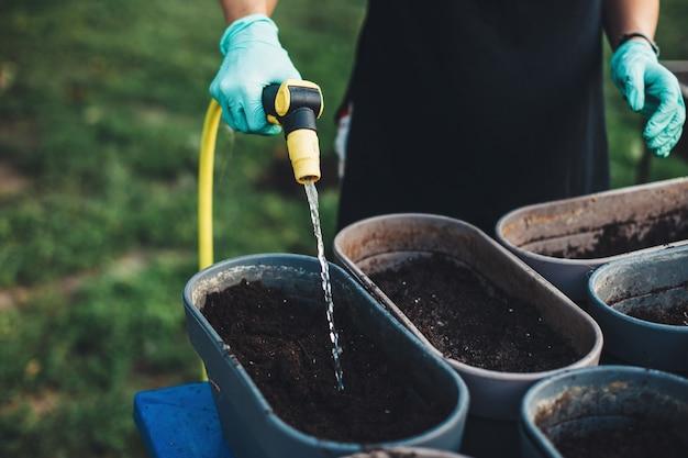 Frau, die samen im topf zu hause wässert, nachdem sie draußen im hinterhof gepflanzt hat