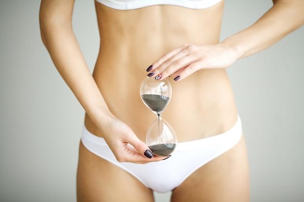 Frau, die sanduhr über ihrem magen hält. gesundheitshygiene-sexualerziehungskonzept
