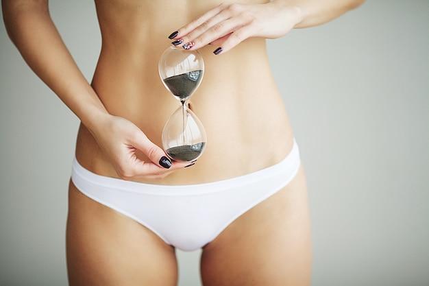 Frau, die sanduhr über ihrem magen hält. konzept der sexuellen aufklärung der gesundheitshygiene