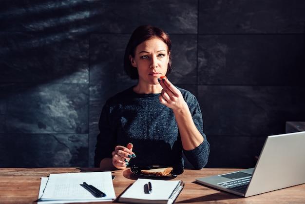 Frau, die sandwich im büro isst