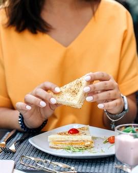 Frau, die sandwich in den händen hält