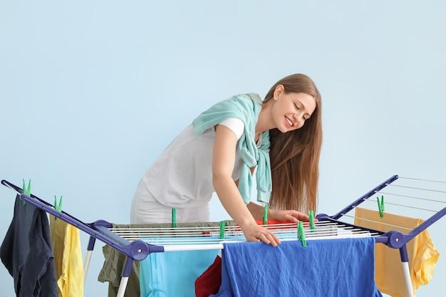 Frau, die saubere kleidung am trockner hängt