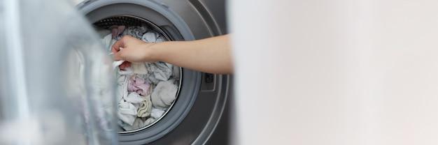 Frau, die saubere kleidung aus der waschmaschine in der badezimmernahaufnahme herauszieht. reparatur und wartung von haushaltsgeräten konzept