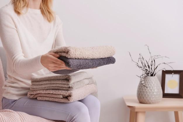 Frau, die saubere weiche handtücher auf sofa zu hause faltet