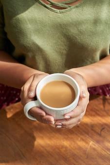 Frau, die schale cappuccino hält