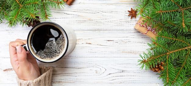Frau, die schale heißen kaffee auf rustikalem holztisch hält. hände in der warmen strickjacke mit becher, wintermorgen oder weihnachtskonzept