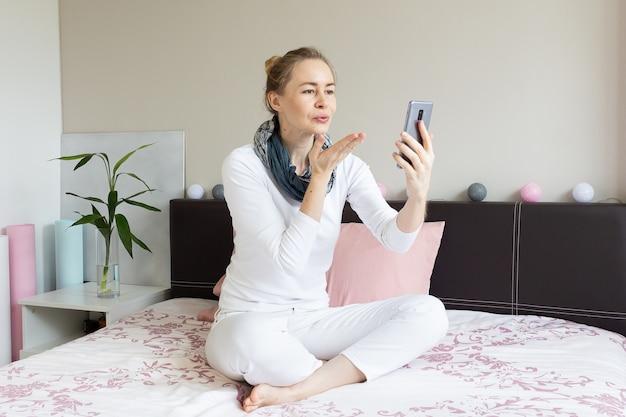 Frau, die schlagkuss während des telefonvideoanrufs sendet.