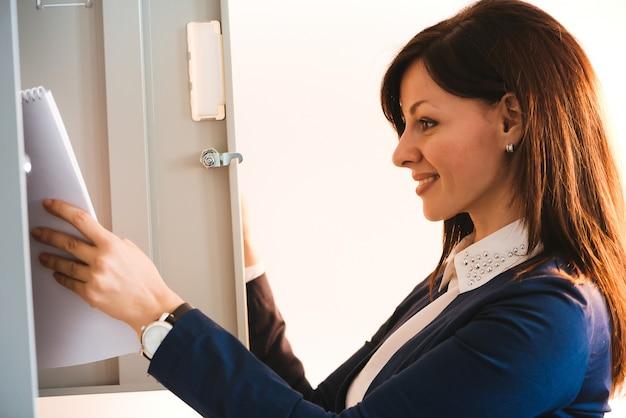 Frau, die schließfach im büro verwendet.