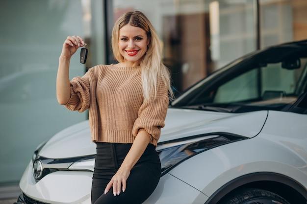 Frau, die schlüssel von ihrem neuen auto hält