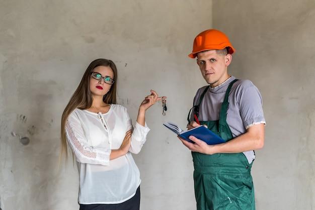 Frau, die schlüssel zum handwerker für renovierung gibt