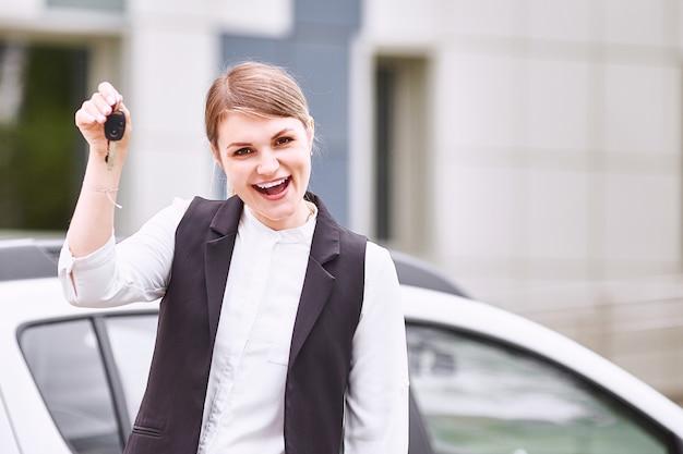 Frau, die schlüssel zum neuwagenauto hält und an der kamera lächelt