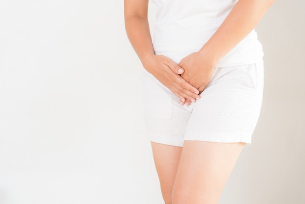 Frau, die schmerzhafte magenschmerzen mit den händen anhalten ihren unterleib der gabelung drückend hat