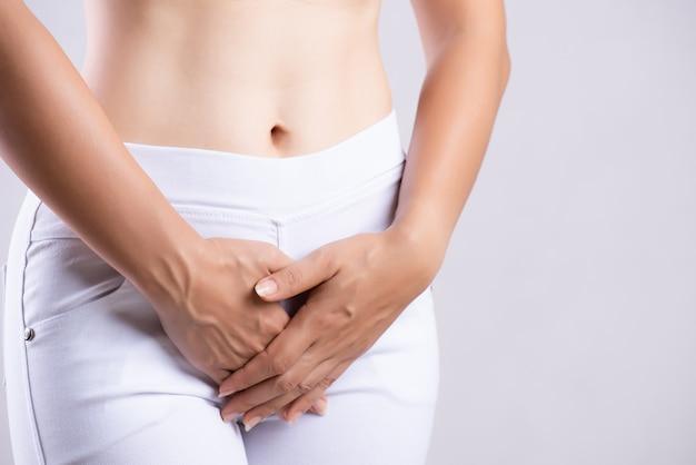 Frau, die schmerzliche magenschmerzen mit den händen halten drückt ihren unteren unterleib der gabelung hat